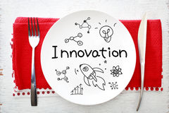 Innovation concept on white plate with fork and knife Stock Photos