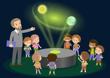 Innovation education elementary school learning technology and people concept - group of kids looking to orbit  earth. hologram on Royalty Free Stock Photo