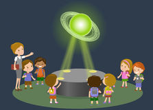 Innovation education elementary school museum astronomy center. Technology and people concept - group of kids looking to. Saturn hologram on physics lesson Royalty Free Stock Photos