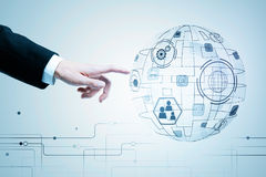 Innovation, global communication and interface concept. Hand pointing at abstract digital globe projection with business icons. Innovation, global communication Stock Image