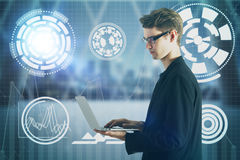 Innovation and hud concept. Side view of handsome young businessman using laptop with abstract business projection in blurry interior with city view. Innovation Royalty Free Stock Image