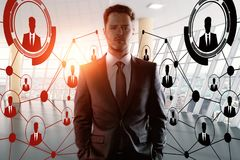 Innovation and human resources concept. Portrait of handsome young businessman standing in modern office interior with abstract HR network. Innovation and human Royalty Free Stock Image