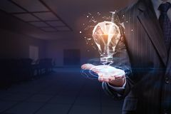Innovation and success concept. Businessman holding abstract glowing polygonal lamp on blurry office interior background. Innovation and success concept. 3D Royalty Free Stock Image