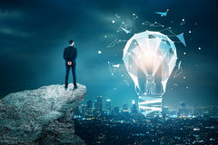 Innovation, technology and idea concept. Back view of young businessman on mountain top looking at night city with abstract low poly light bulb. Innovation