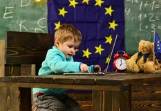 Innovation and technology. Little child use laptop computer in classroom with eu flag, innovation. Innovation in. Elementary school. Extending your reach with stock photos