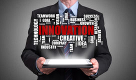 Innovation word cloud concept appearing above a tablet. Businessman holding a tablet with innovation word cloud concept stock photos