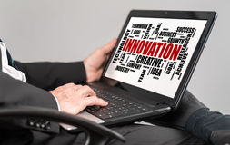 Innovation word cloud concept on a laptop. Businessman watching innovation word cloud concept on a laptop royalty free stock photo