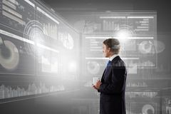 Innovations in business. Young businessman with cup in hand looking at media screen Stock Image