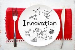 Innovationskonzept auf weißer Platte mit Gabel und Messer Stockfotos
