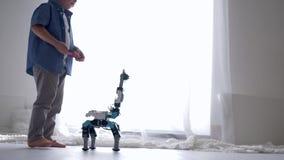 Innovationstechnologie in der Kindheit, netter Kinderjunge wird durch Roboterspielzeug auf Fernbedienung unter Verwendung des Han stock video
