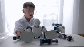 Innovationteknologi, liten teknikerpojke som monterar den Humanoid roboten med konstgjord intelligens arkivfilmer
