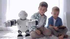 Innovativ framtid kontrollerar klyftiga barn den humanoid roboten genom att använda en mobiltelefon på golvet hemma lager videofilmer