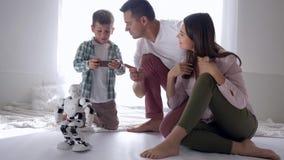 Innovativ framtid lycklig modern familj som spelar med den humanoid roboten som tillsammans sitter på golv på helgen stock video