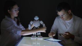 Innovativa teknologier, ung elektroniktekniker som samarbetar på konstruktion av den Humanoid roboten i seminarium stock video