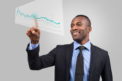 Innovative business. Cheerful young African man in formalwear pointing diagram on the transparent wipe board while standing against grey background Royalty Free Stock Photos
