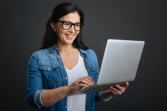 Innovative graceful lady employing her gadget for work. Convenient communication. Smart focused stunning woman using her laptop for writing an email and Stock Photo