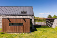 Innovative house with pebble walls. Innovative house in the country, with pebble walls, wooden garage and metal fence stock photography