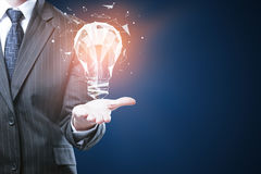 Innovative ideas concept. Businessman holding glowing polygonal lamp on blue background with copyspace. Innovative ideas concept royalty free stock photos