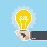 Innovative Idee - Glühlampe in der Hand Lizenzfreie Stockfotos