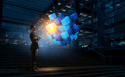 Innovative technologies integration. Mixed media. Businessman in dark office and cube figure. Mixed media Stock Images