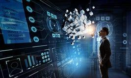 Innovative technologies integration. Mixed media. Businessman in dark office and cube figure. Mixed media Stock Photos
