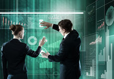 Innovative technologies. Rear view of businessman and businesswoman working with virtual panel interface Stock Images