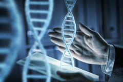 Innovative technologies in science and medicine. Hands of businessman using virtual panel and DNA molecule Royalty Free Stock Image