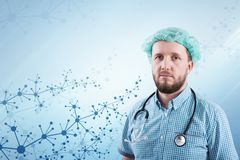 Handsome male doctor against an abstract medical background with molecular lattice. Innovative technologies in science and medicine. Handsome male doctor against Royalty Free Stock Images