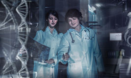 Innovative technologies in science and medicine. Mixed media. Group of young geneticists working with virtual screen. Mixed media Royalty Free Stock Image