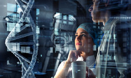 Innovative technologies in science and medicine. Mixed media. Group of young geneticists working with virtual screen. Mixed media Royalty Free Stock Photo