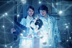 Innovative technologies in science and medicine. Young thoughtful doctors looking at holographic image Royalty Free Stock Photos