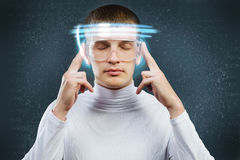 Innovative technologies. Young handsome man in glasses and virtual headphones Royalty Free Stock Images