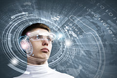Innovative technologies. Young man wearing futuristic glasses against blue background Stock Image