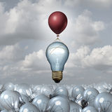 Innovative Thinking Concept. As a group of 3D illustration light bulbs in a vast landscape as one lightbulb rises up with the help of a balloon as a motivation Stock Image