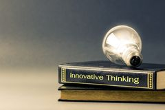Innovative thinking. Light bulb glowing on the Innovative Thinking book royalty free stock images