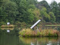 Innovative Use of Solar Panels on Lake in Forest. Innovative use of solar panels placed on a small islands to catch open sunlight in forest setting royalty free stock images
