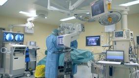 Innovativt medicinbegrepp En kirurg använder det moderna mikroskopet och den kirurgiska roboten under en kirurgi på en klinik stock video