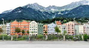 INNSBRUCK, AUSTRIA - JULY 31, 2017: Colorful houses on the bank of Inn river. Alps in background. Innsbruck is the capital of the Tirol. Famous destination both Stock Images