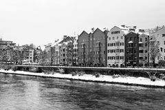 View of the Inn river in winter in Innsbruck, Austria during the early morning, trees and mountains. Black and white Royalty Free Stock Photography