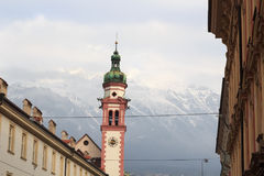 Innsbruck cityscape with church spire and snow mountains. Austria stock photography
