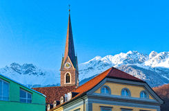 The Innsbruck places. Austria, Tirol, Innsbruck, view of  the snowy mountains fom the Inn river bank with old houses and bell tower in the foreground Stock Images