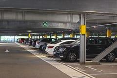 Inom av den mörka fria mång- våningsparkeringshuset som tillhör köpcentret med parkerade bilar i Tyskland arkivbilder