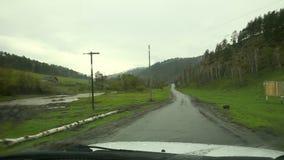 Inom av en bil chaufförställepunkt av sikten som kör landsvägen på den regniga väderdagen Regndroppar på en vindruta A stock video