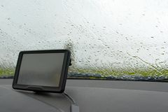 Inom av en bil med regn på vindrutafönster- och GPS navigeringsystem i dåligt väder royaltyfri bild