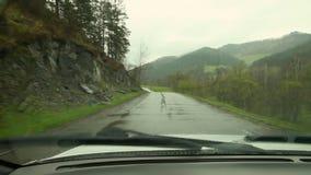 Inom av en bil tappar chaufförställepunkt av sikten som kör landsvägen på den regniga väderdagen, vatten Regndroppar på a lager videofilmer