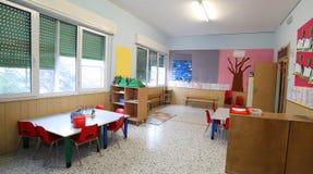 Inom av ett klassrum med stolar och bänkar Arkivfoto