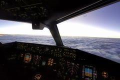 Inom cockpit av flygplanet över himmel royaltyfri foto