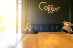 """Inom den dekorativa svarta soffan för modern coffee shop och trätabeller och handstil för """"coffee""""ord med neonljus royaltyfri foto"""