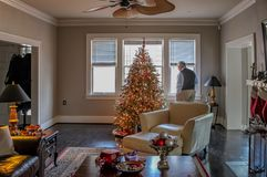 Inom det eleganta hemmet som dekoreras för jul med trädet och strumpor ser en äldre man, ut fönstret arkivfoton