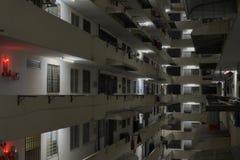Inom det inhysa komplexa kvarteret med hängande kläder och röda ljus arkivfoto